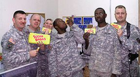 Soldiers from Iraq holding Sugar Babies candy boxes